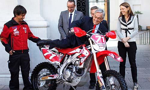 Sebastián Piñera se sube a una moto en la confirmación del Dakar 2011.
