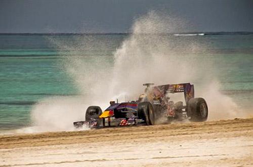 Alguersuari al mando de un Fórmula 1 de Red Bull en la playa de República Dominicana.