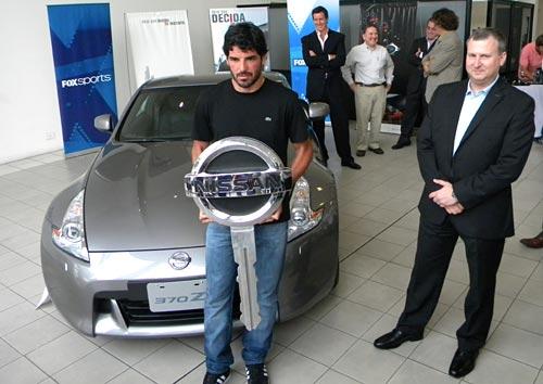 Tuzzio con la llave gigante de Nissan y su 370Z detrás