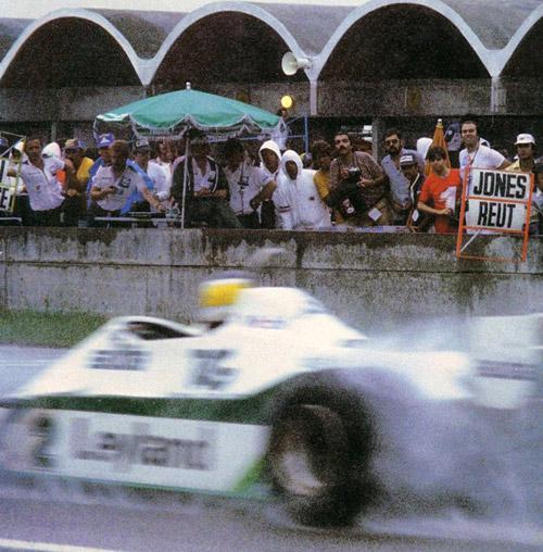 Pasa Reutemann sin mirar el cartel que le muestran en boxes.