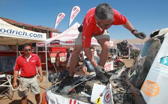 Los Loctite Charlies reparando un parabrisas en el Dakar 2012.