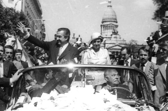 Alfonsín y su esposa Lorenza saludan en el Cadillac presidencial.